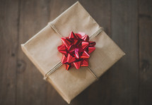 gift wrapped in brown paper and a red bow