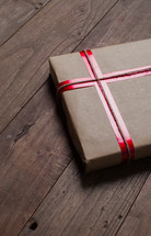 wrapped gift in brown paper and red ribbon
