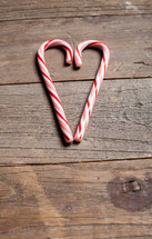 candy canes in the shape of a heart on a wood floor