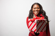 Joyful woman presenting a Christmas gift.