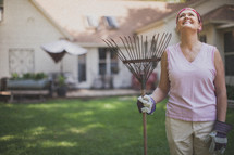 woman holding a rake and looking up to God