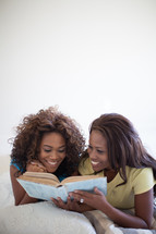 sisters reading a Bible together