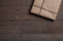 gift wrapped in brown paper on a wood floor