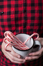 man in a plaid shirt holding a mug of candy canes