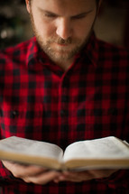 a man in a plaid shirt reading a Bible