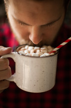 a man in a plaid shirt drinking a mug of hot chocolate