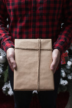 man in a plaid shirt holding a wrapped gift