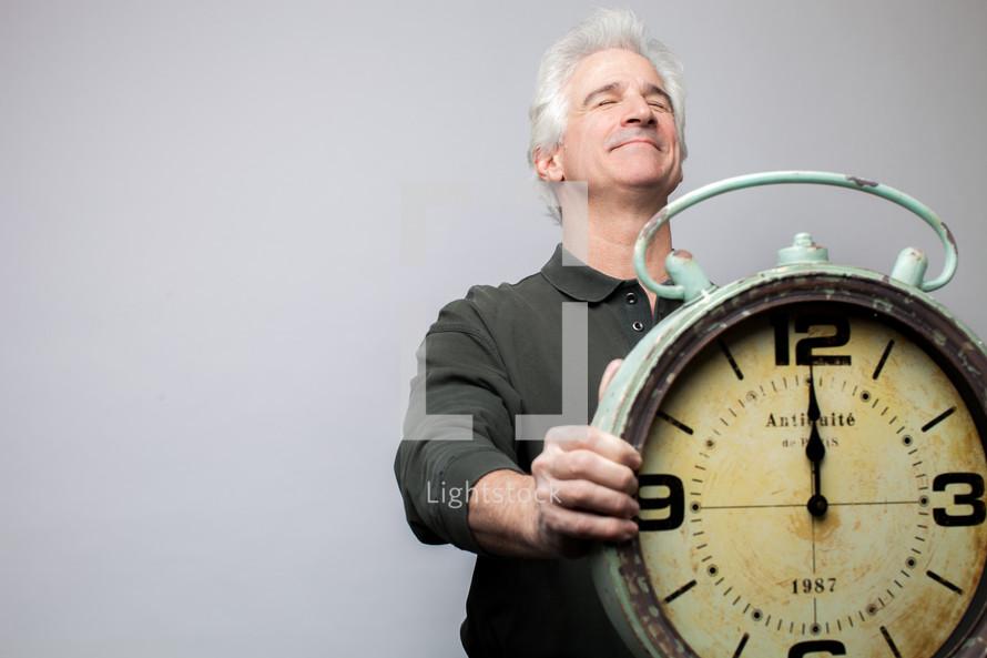 man holding a clock at midnight