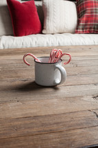 red and white pillows on a couch and candy canes in a mug on a wood table