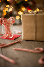 wrapped gift and candy canes spread out on a wood floor