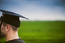 Graduate in a field of green grass.