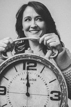 woman holding a clock at midnight