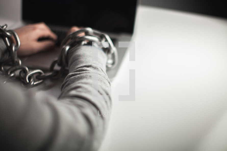 Wrists bound with chains working on laptop computer.