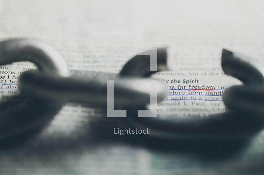 A Bible verse seen through a broken chain link.