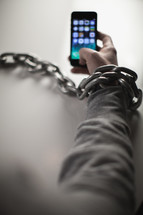 man bound in chains on a cellphone