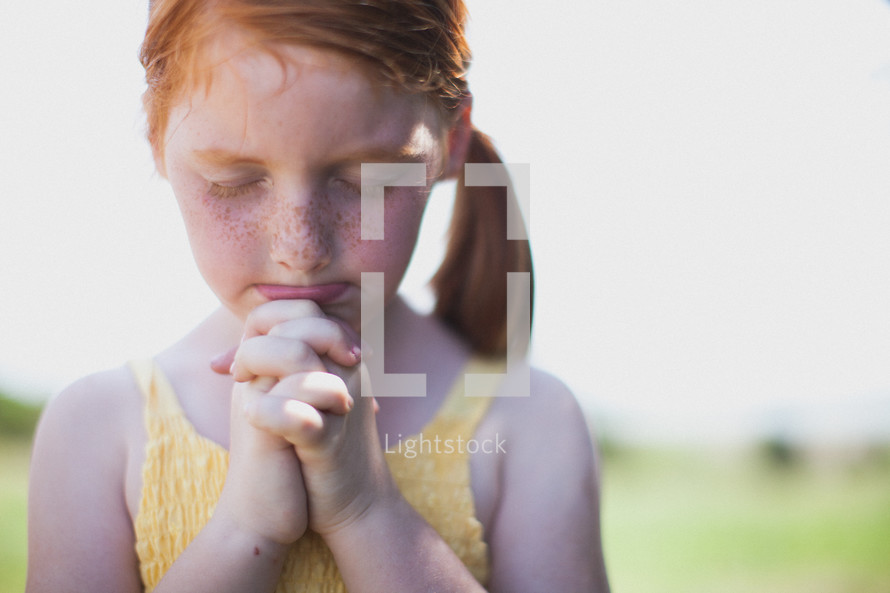 young freckled face girl in prayer