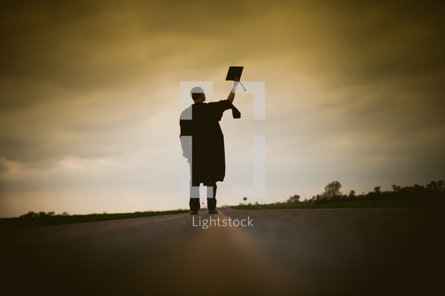 Graduate holding cap in the middle of the road.