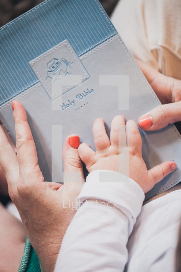 mother and infants hand on a Bible