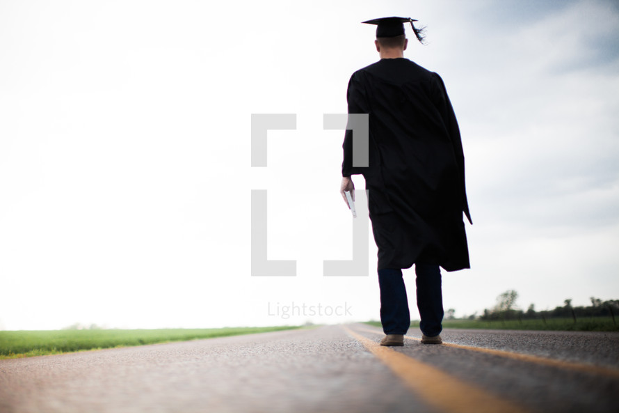 Graduate holding a Bible walking down the middle of the road.