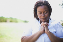 Woman praying outside.