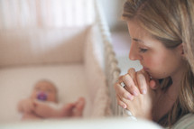 mother praying over a baby in a crib