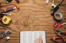 man pointing to a Bible surrounded by tools