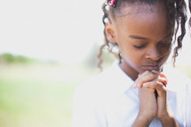 young African-American girl with praying hands