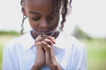 Girl praying outside.