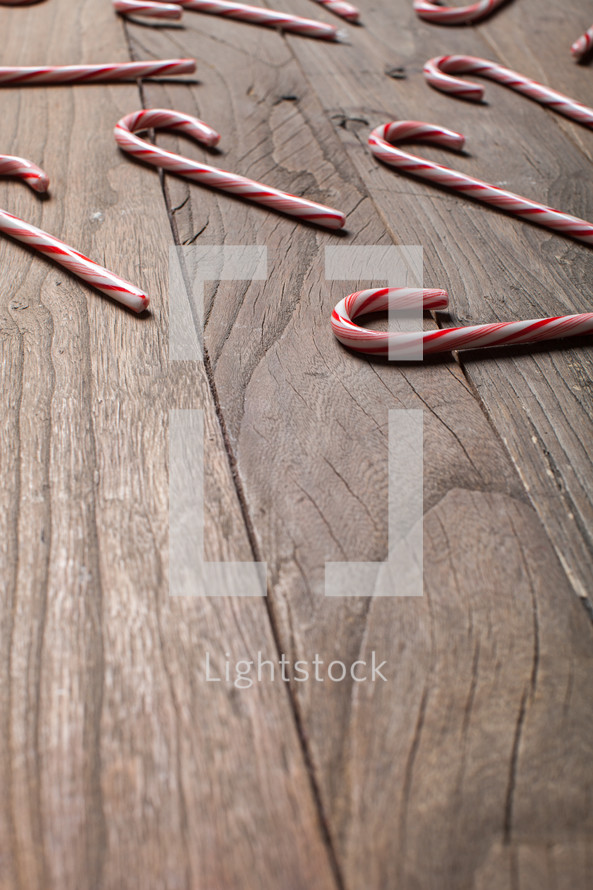 candy canes spread out on a wood floor