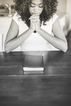 Woman praying over closed bible.