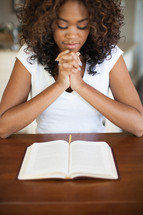 woman in prayer over a Bible