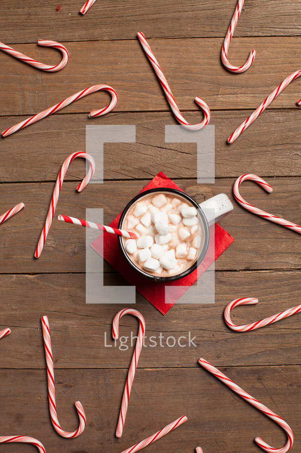 candy canes spread out on a table and a mug of hot cocoa