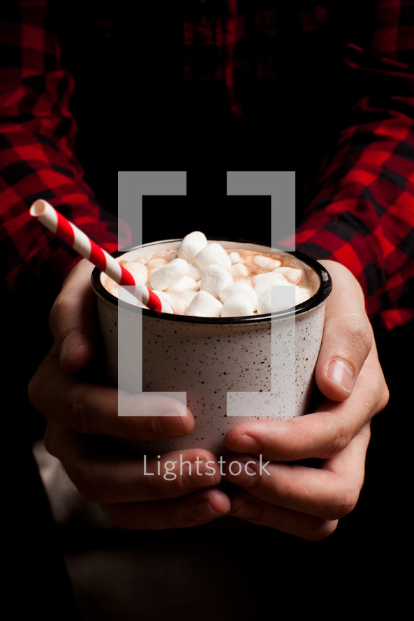 a man in a plaid shirt holdig a mug of hot chocolate