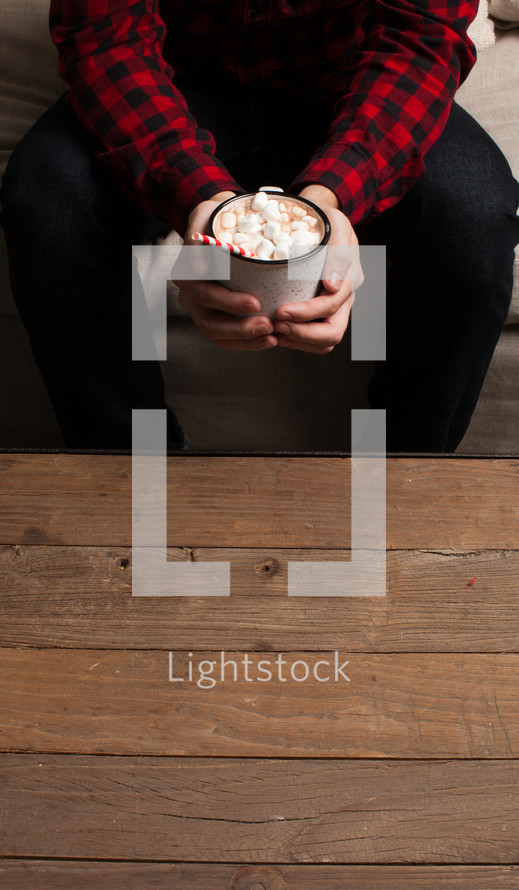 a man holding a mug of hot cocoa