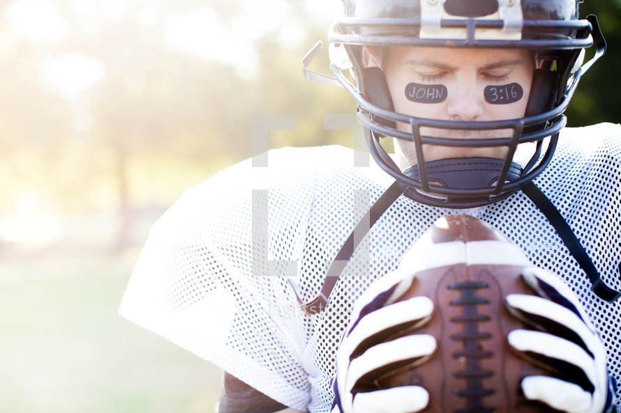 football player holding a football praying