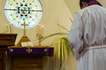 A pastor bows his head before a church altar.
