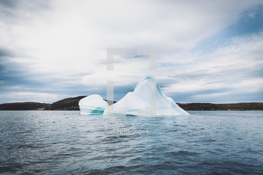 An iceberg sticking out of a body of water.