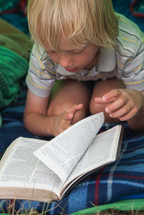 child reading a Bible in a tent and sleeping bag