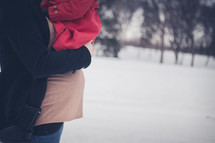 expecting mother hugging her older child