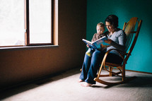 mother reading to her son sitting in a rocking chair