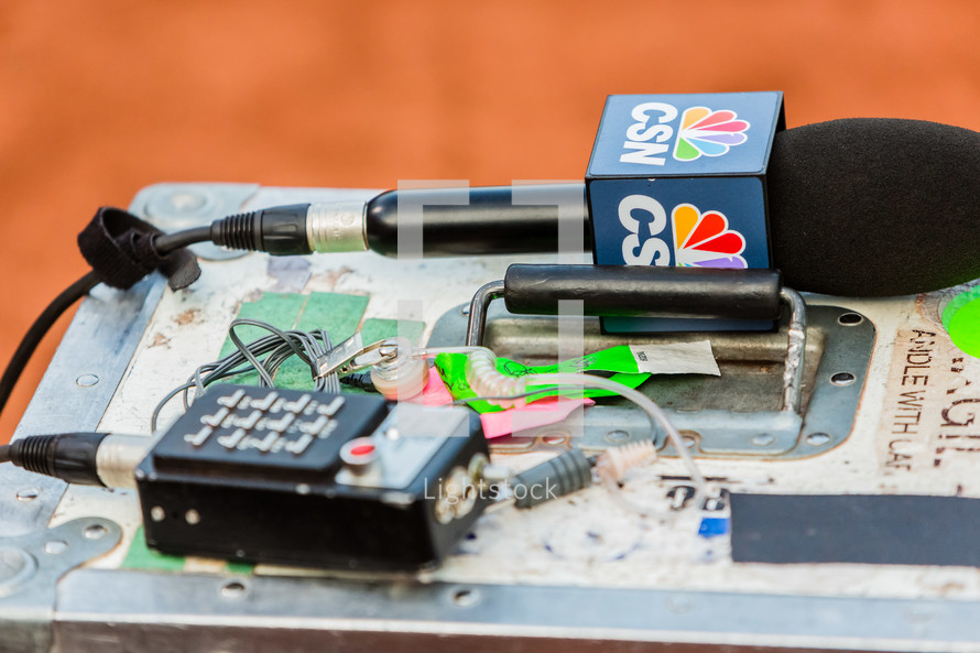 News reporter gear and microphone with nbc in-ear on a box.
