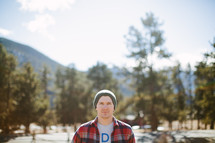 man in a plaid shirt standing outdoors