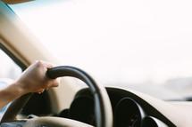 hand on a steering wheel