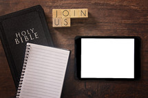 Bible and notebook on a wood background - join us