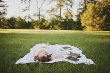 woman lying on a blanket in the grass next to books