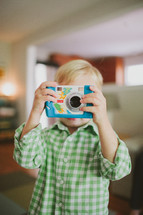 child taking a picture with a camera