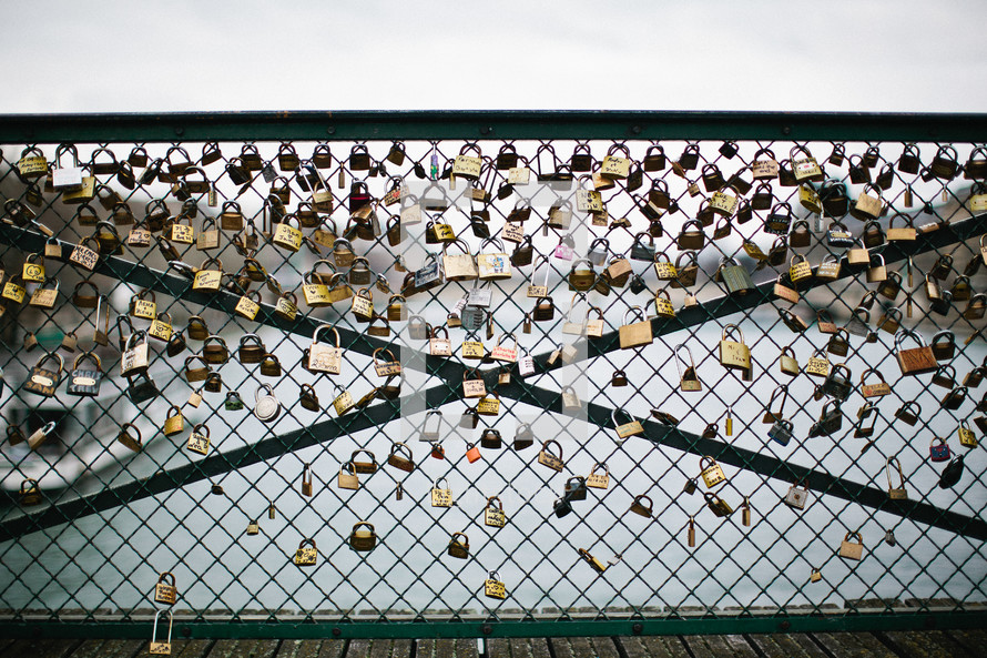 A chain link fence on a bridge covered in locks