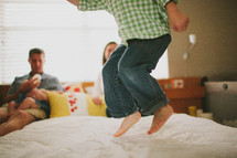 mother and father watching a toddler boy jumping on a bed