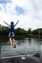 child jumping into a lake