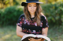 teen girl in a hat reading a Bible outdoors